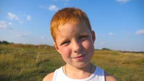 Portret młoda czerwona włosiana chłopiec z piegów ono uśmiecha się plenerowy Uroczy dziecko patrzeje w kamerę z radosnym uśmieche zbiory wideo