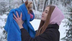 Portret młoda dziewczyna całuje Yorkshire teriera trzyma psa zawijający w błękitnej koc w zima śnieżystym parku A zbiory wideo
