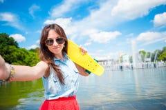 Portret młoda dziewczyna ma zabawę z deskorolka w parku Stylu życia portret młoda pozytywna kobieta ma zabawę i Zdjęcie Stock