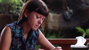 Portret Młoda freelancer kobieta używa smartphone, kąski jej wargi, poważne, działanie nerwowy, ruchliwie, stres, kawiarnia zbiory