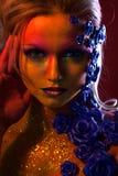Portret młoda i atrakcyjna kobieta z sztuki makeup Ogniści kolory, błyskotliwość na twarzy i kwiecista dekoracja, Fotografia Stock