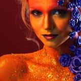 Portret młoda i atrakcyjna kobieta z sztuki makeup Ogniści kolory, błyskotliwość na twarzy i kwiecista dekoracja, Obrazy Royalty Free