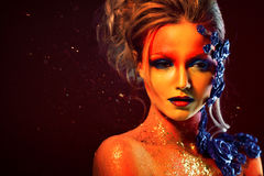 Portret młoda i atrakcyjna kobieta z sztuki makeup Ogniści kolory, błyskotliwość na twarzy i kwiecista dekoracja, Obrazy Stock