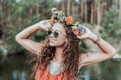 Portret młoda kędzierzawa kobieta z kwiecistym chaplet cieszy się weekend w lesie zdjęcie stock