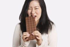 Portret młoda kobieta je wielkiego czekoladowego baru nad światłem - szary tło Obrazy Stock