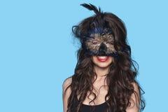 Portret młoda kobieta jest ubranym egzotyczną oko maskę nad błękitnym tłem Zdjęcia Royalty Free