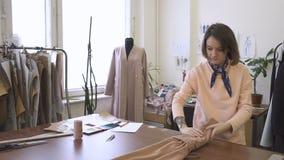 Portret młoda kobieta która pakuje brąz suknię w jej studiu, zdjęcie wideo