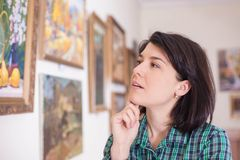 Portret młoda kobieta patrzeje obraz w muzeum lub galeria sztuki fotografia royalty free