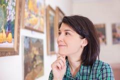 Portret młoda kobieta patrzeje obraz w muzeum lub galeria sztuki zdjęcie royalty free