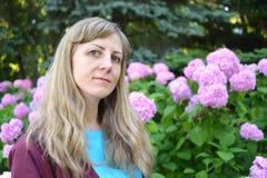 Portret młoda kobieta przeciw tłu kwitnie hortensja lata ogrodu Zdjęcie Stock