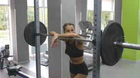 Portret młoda kobieta przygotowywa podnosić ciężkich barbells przy gym Żeńska atleta bierze barbell z ciężkimi ciężarami Zdjęcia Stock