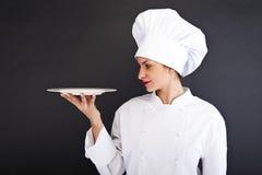 Portret młoda kobieta szef kuchni z talerzem zdjęcie royalty free