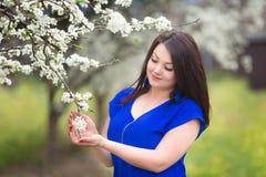 Portret młoda kobieta trzyma śniadanio-lunch kwitnąć śliwkowego drzewa w sadzie zdjęcia stock