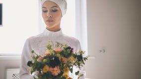 Portret młoda kobieta trzyma bukiet kwiaty w tradycyjnej islamskiej ślubnej sukni Obrazy Royalty Free