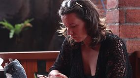 Portret młoda kobieta używa smartphone, kąski jej wargi, poważne, działanie nerwowy, ruchliwie, stres, kawiarnia w Bali zdjęcie wideo