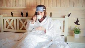 Portret młoda kobieta w bathrobe obsiadaniu w łóżku i pić herbacie obrazy stock