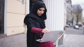 Portret młoda kobieta w czarnym hijab obsiadaniu na drewnianej ławce i używać jej laptop Studiowanie lub działanie Slowmotion zbiory wideo