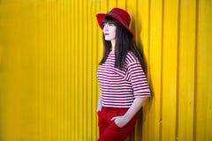 Portret młoda kobieta w czerwieni pozuje nad kolor żółty ścianą z kopią obraz stock