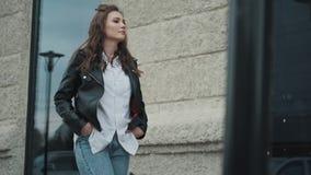 portret młoda kobieta w skórzanej kurtce na ulicie Modniś dziewczyny odprowadzenie w mieście zbiory wideo
