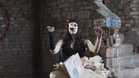 Portret młoda kobieta z białą twarzą podmuchową za ogieniu w zaniechanym budynku przed ścianą Przedstawienie zbiory