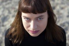 Portret młoda kobieta z & x28; kako se zove jajeczek frizura & x29; i zieleni oczy patrzeje kamerę z piaskiem w tle Obrazy Royalty Free