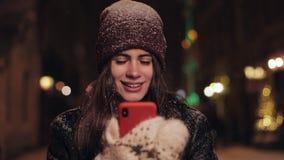 Portret młoda kobieta z smartphone miasta chodzącą ulicą przy nocą Kobieta używa app na smartphone w mieście przy nocą zbiory wideo