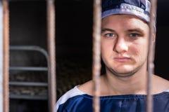 Portret młoda męskiego więźnia pozycja za więźniarską siatką wewnątrz Obrazy Stock