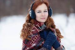 Portret młoda miedzianowłosa kobieta w błękitnych hełmofonach Zdjęcia Stock