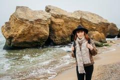 Portret młoda miedzianowłosa kobieta w kapeluszu i szaliku z plecakiem przeciw tłu skały przeciw fotografia stock
