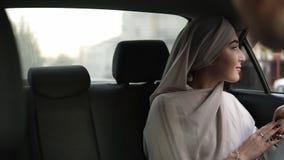 Portret młoda muzułmańska kobieta w beżowej chustce na głowę, siedzi w samochodzie podczas gdy przyglądający za okno przez wtedy zbiory wideo