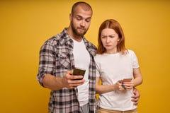 Portret młoda pary pozycja z telefonem komórkowym, mężczyzna używa telefon komórkowego podczas gdy gniewna dziewczyna stoi blisko fotografia royalty free