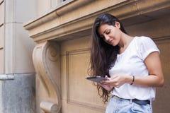 Portret młoda piękna łacińska kobieta używa cyfrową pastylkę podczas gdy stojący na ulicie przeciw budynek ścianie z kopii przest Zdjęcia Stock