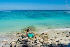 Portret młoda piękna azjatykcia uśmiechnięta dziewczyny pozycja na skałach przy plażą Obraz Stock
