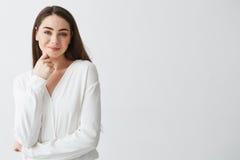Portret młoda piękna biznesowa dama patrzeje kamery macania uśmiechniętą twarz nad białym tłem Zdjęcia Royalty Free