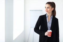 Portret młoda piękna biznesowa kobieta z filiżanką kawy wewnątrz Zdjęcia Stock