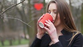 Portret młoda piękna blondynka modnisia kobieta pozuje na jesień parka tle i pije filiżankę takeaway zbiory wideo