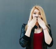 Portret młoda piękna blondynki dziewczyna zamyka usta jej ręki w niespodziance Obrazy Stock