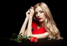 Portret młoda piękna blondynki kobieta w czerwieni sukni z czerwienią r Zdjęcie Royalty Free