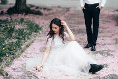 Portret młoda piękna brunetki dziewczyna w białym ślubnej sukni obsiadaniu na trawie w kwitnącym wiosna ogródzie Zdjęcie Stock