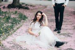 Portret młoda piękna brunetki dziewczyna w białym ślubnej sukni obsiadaniu na trawie w kwitnącym wiosna ogródzie Obrazy Stock