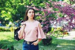 Portret młoda piękna dziewczyna pozuje modela na ulicach Europejski miasto na tle kwiatonośni drzewa, Zdjęcia Stock