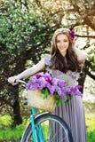 Portret młoda piękna dziewczyna z długie włosy w jaskrawej sukni z kwiatami w koszu na rocznika rowerze fasonująca kobieta obrazy stock