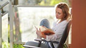 Portret Młoda Piękna dziewczyna Z Kaukaskim pojawieniem Czyta Ciekawego Książkowego obsiadanie Na balkonie kobieta relaksuj?ca zbiory wideo