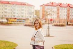 Portret młoda piękna kobieta ono uśmiecha się kamera w mieście na bulding tle w pogodnym wiosna dniu zdjęcia stock