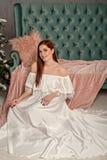 Portret młoda piękna kobieta w białym eleganckim wieczór sukni obsiadaniu na podłogowej pobliskiej kanapie zdjęcie royalty free
