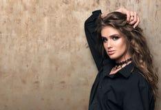 Portret młoda piękna kobieta w czarnej koszula pozuje przed metal ścianą zdjęcie royalty free