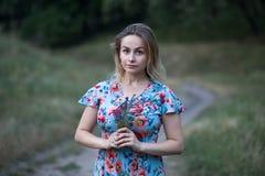 Portret młoda piękna kobieta w kwiat sukni mieniu kwitnie w ona ręki Obraz Stock