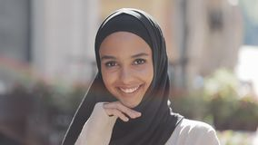 Portret młoda piękna muzułmańska kobieta jest ubranym hijab chustki na głowę śmiać się rozochocony w starym mieście z bliska zdjęcie wideo