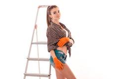 Portret młoda plciowa brunetka budynku kobieta z drabiną robi odświeżaniu i pozować na kamerze odizolowywającej na bielu Obrazy Stock