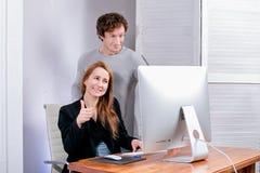 Portret młoda pomyślna kobieta i mężczyzna przy biurem Patrzeją pokazu approvingly Black Friday Poniedziałek lub Cyber target218_ fotografia royalty free
